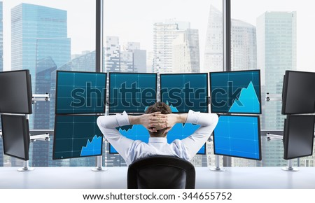 man with hands locked on back of the head sitting in front of monitors, processing data for trading, singapore at the background - stock photo