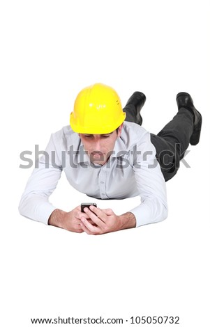 Man with hard hat looking at his mobile