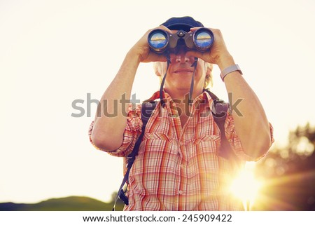 Man with hat and binoculars against the light