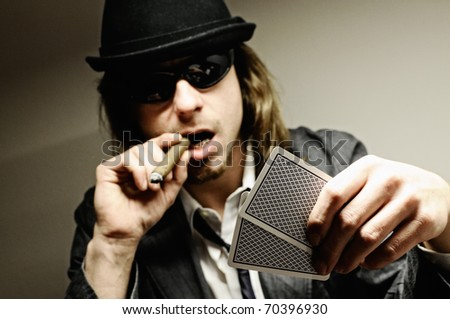 Man with hat and cigar playing underground poker.