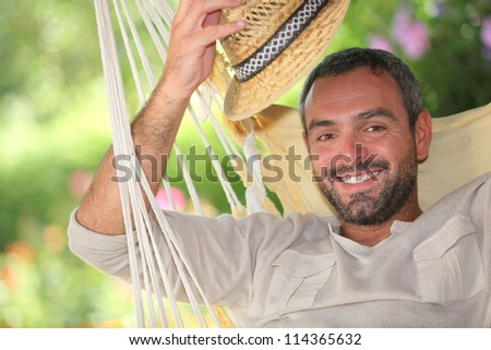Man with hat on hammock - stock photo