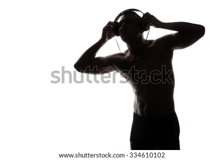 man with headphones listening to music - beautiful male body - athletic torso  - stock photo