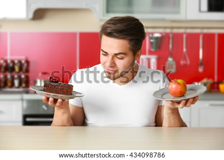 Man with healthy and unhealthy food in kitchen - stock photo