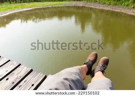 Man with hiking shoes on wooden floor - stock photo
