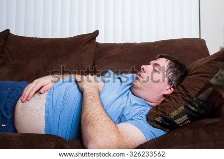 Man with his belly hanging out laying on the couch tired and asleep - stock photo
