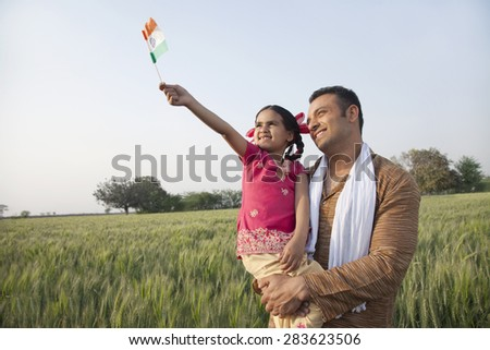 Man with his daughter holding Indian flag in an agricultural field - stock photo