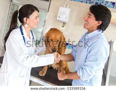 Man with his dog giving handshake to a doctor at the vet - stock photo