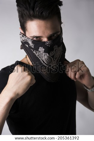 Man with his face hidden behind a bandanna balling his fists aggressively and raising them threateningly as he stares balefully at the camera - stock photo