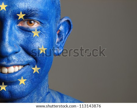 Man with his face painted with the flag of European Union. The man is smiling and photographic composition leaves only half of the face. - stock photo