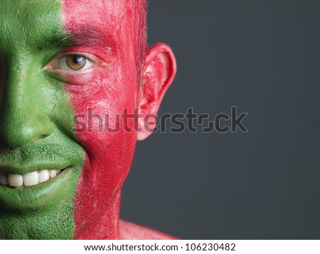 Man with his face painted with the flag of Portugal. The man is smiling and photographic composition leaves only half of the face. - stock photo