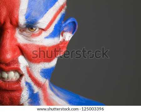 Man with his face painted with the flag of United Kingdom. The man is angry and photographic composition leaves only half of the face. - stock photo