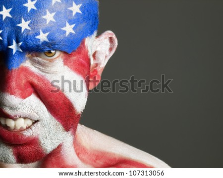 Man with his face painted with the flag of USA. The man is aggressive and photographic composition leaves only half of the face.