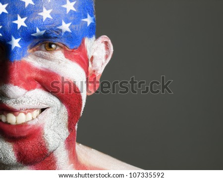 Man with his face painted with the flag of USA. The man is smiling and photographic composition leaves only half of the face. - stock photo