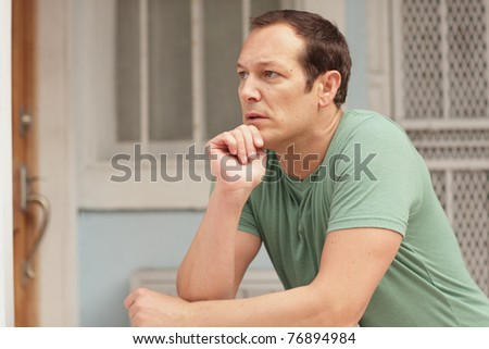 Man with his hand under his chin - stock photo