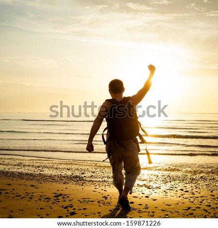 Man with his hands up on the dawn on the beach - stock photo