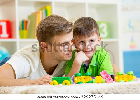 man with his kid son playing together at home - stock photo