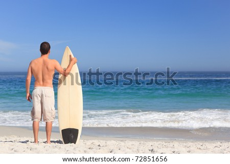 Man with his surfboard on the beach - stock photo