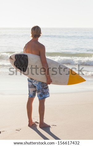 Man with his surfboard on the beach looking out to sea - stock photo