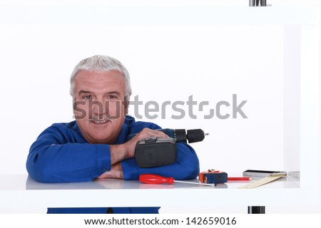 Man with his tools leaning on a shelf - stock photo