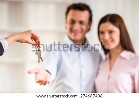 Man with his wife being given a house key. - stock photo