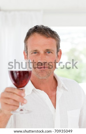 Man with his wineglass in his kitchen at home - stock photo