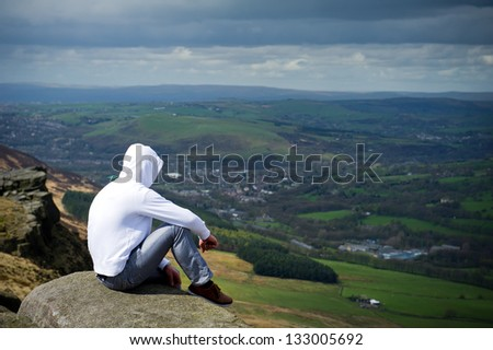 man with hood sitting on cliff and looking to a view - stock photo