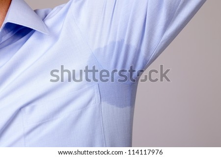 Man with hyperhidrosis sweating very badly under armpit in blue shirt, isolated on grey - stock photo