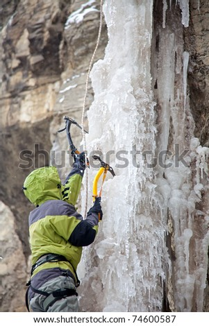 Man with ice axes climbing on icefall - stock photo