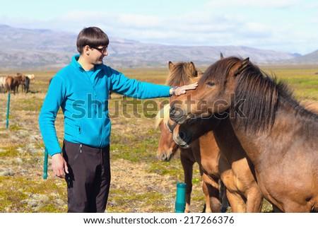 Man with icelandic horses - stock photo