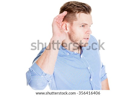 Man with impaired hearing struggling to hear frowning as he holds his hand to his ear in an attempt to improve acoustics - stock photo
