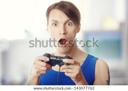 Man with joystick playing horror computer game - stock photo