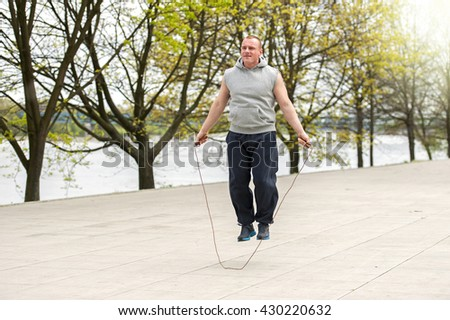 Man with jump rope in park.