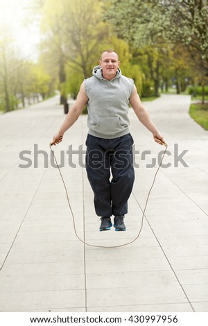 Man with jump rope in park. - stock photo