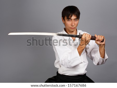 Man with katana sword on grey background standing in fighting pose. - stock photo