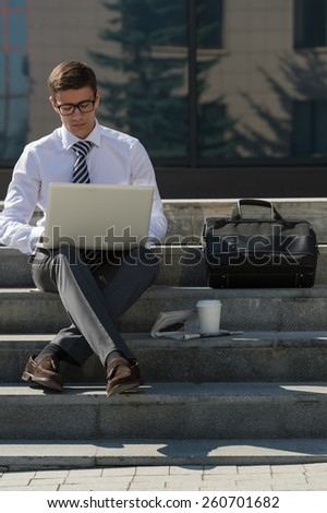 Man with laptop and coffee at summer park on bright day - stock photo