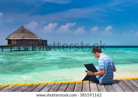 man with laptop and mobile sitting on a wooden bridge near the water bungalows, of background colorful beach of island  - stock photo