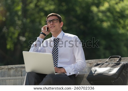 Man with laptop calling by phone at summer park on bright day - stock photo