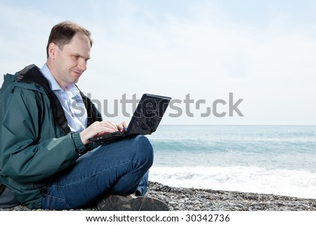 Man with laptop on beach - stock photo