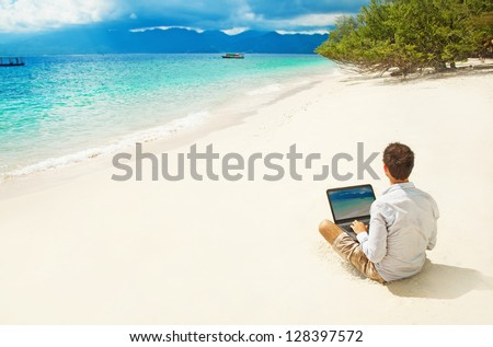 man with laptop on colorful beach of island - stock photo