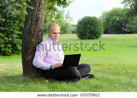 man with laptop sitting near a tree in the green park