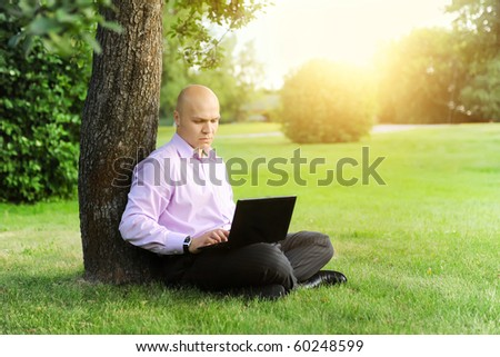 man with laptop sitting near a tree in the park - stock photo