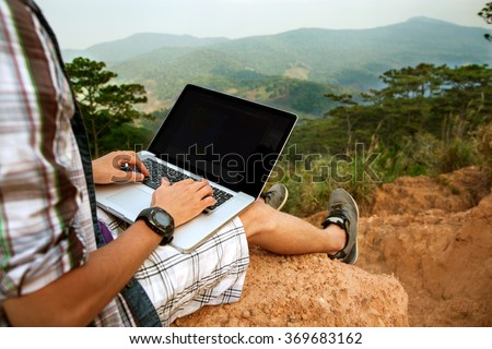 man with laptop sitting on the edge of a mountain with stunning views of the valley - stock photo
