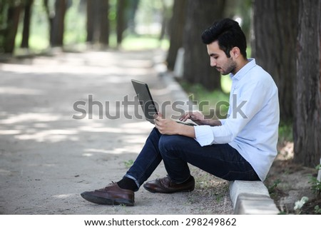 Man with laptop success outside sitting  - stock photo