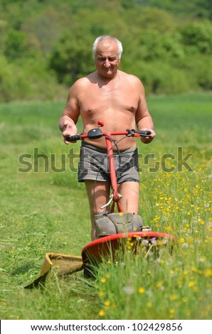 man with lawn mower cutting grass. - stock photo