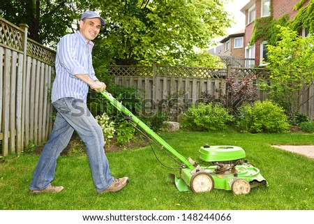 Man with lawn mower in landscaped backyard - stock photo