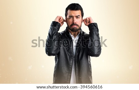Man with leather jacket covering his ears