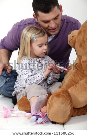 Man with little girl playing with teddy bear - stock photo