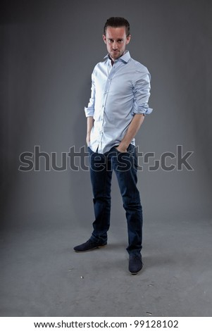 Man with long hair and expressive face wearing blue shirt. Looking down. Isolated on grey background. - stock photo