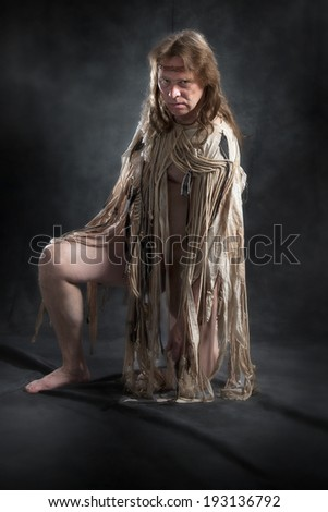 man with long hair in the ancient character posing on a black background