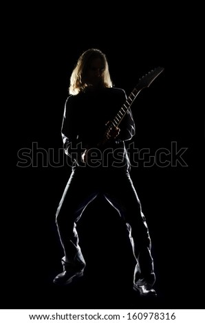 Man with long hair playing guitar against a black background